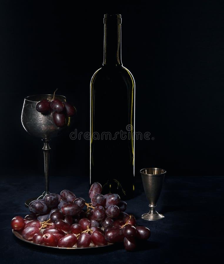 黑暗的瓶、葡萄酒库和玻璃 库存照片