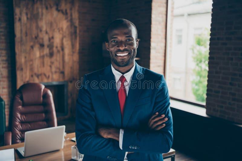 黑暗的皮肤人最佳的贸易商照片佩带典雅的服装坐的办公室椅子 库存图片