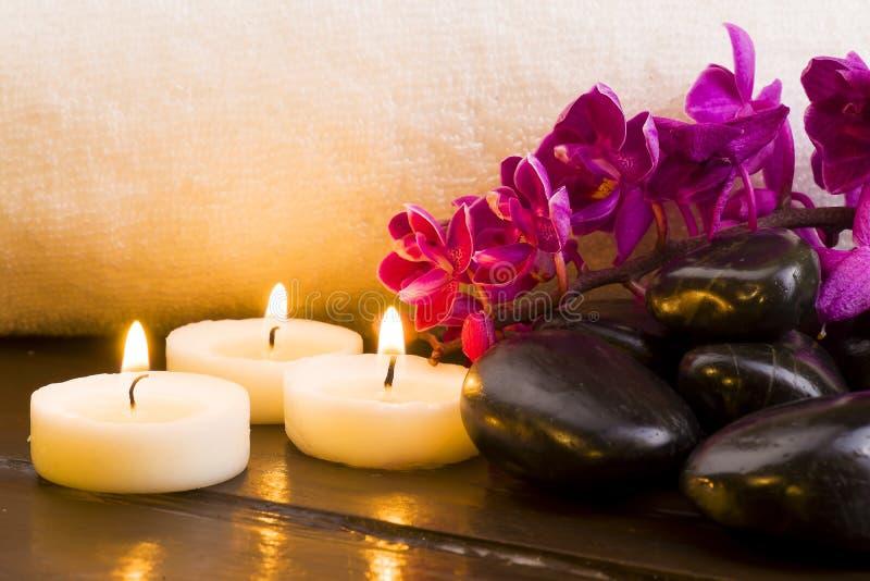 黑暗的石头和蜡烛和兰花在白色毛巾背景 库存图片