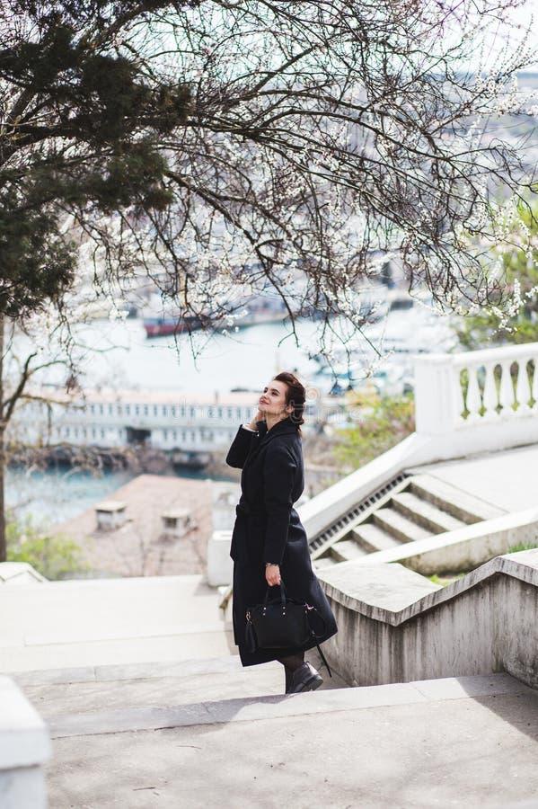 黑暗的羊毛外套的美丽的年轻女人在春天的街道 杏仁花开花,佩带的时髦外套 免版税图库摄影