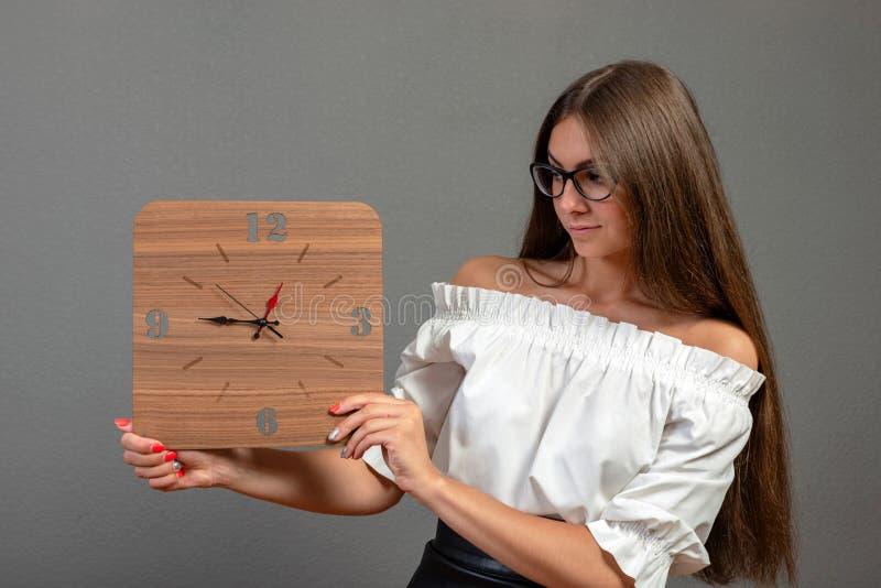 黑暗的背景的可爱,情感年轻女人显示一个时钟-图象 库存图片