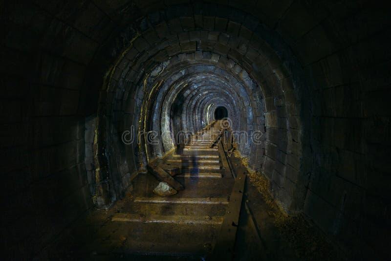 黑暗的蠕动的肮脏的被充斥的被放弃的矿隧道 免版税库存图片