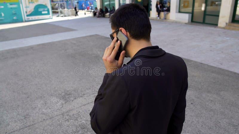 黑暗的衣服的大忙人讲话在电话和走的城市街道,活跃生活 图库摄影