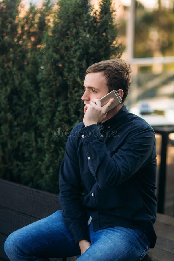 黑暗的衬衣电话的年轻人某人 r 免版税库存照片