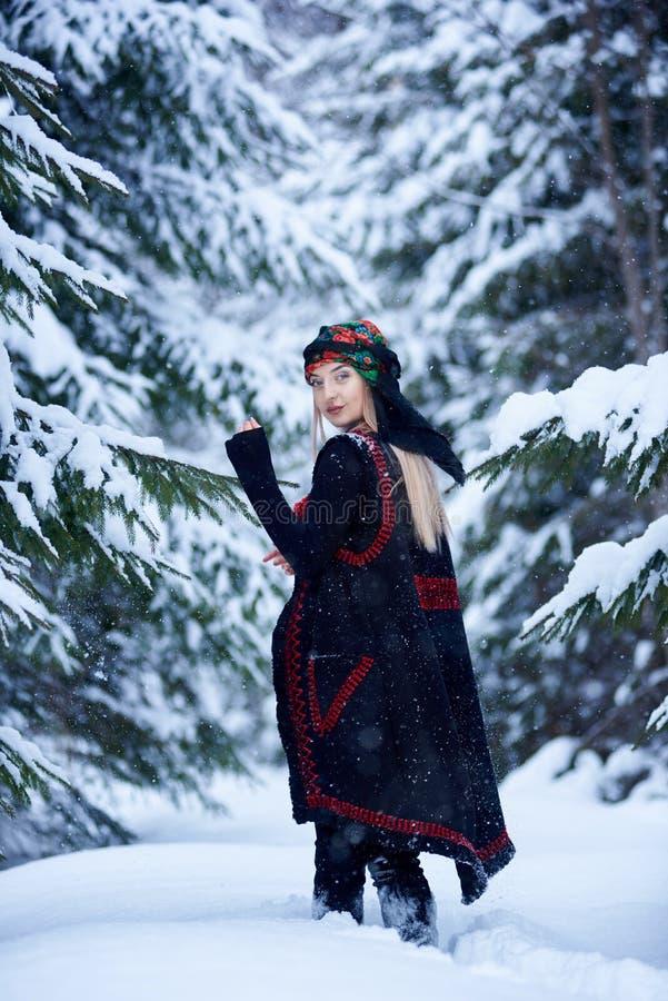黑暗的被绣的长的无袖的外套和方巾的可爱的女孩有花卉设计的户外 库存图片