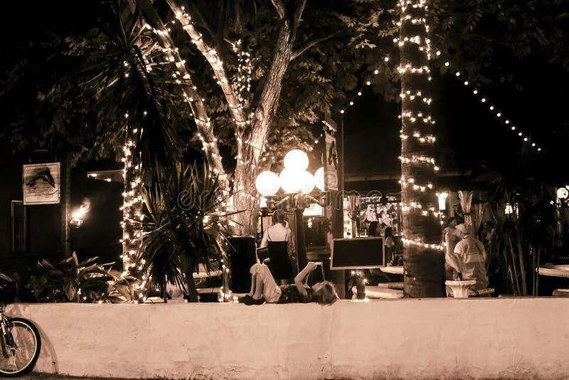 黑暗的赭色iage室外resturant与在热带说谎在有她的手机的墙壁上的树和小女孩附近的光为 库存图片