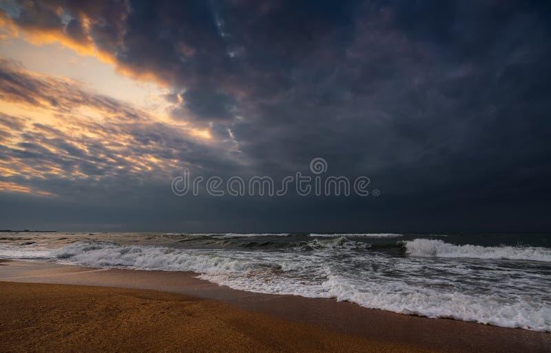 黑暗的风雨如磐的海和空的海滩 免版税库存照片