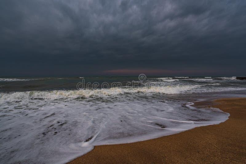 黑暗的风雨如磐的海和空的海滩 免版税图库摄影