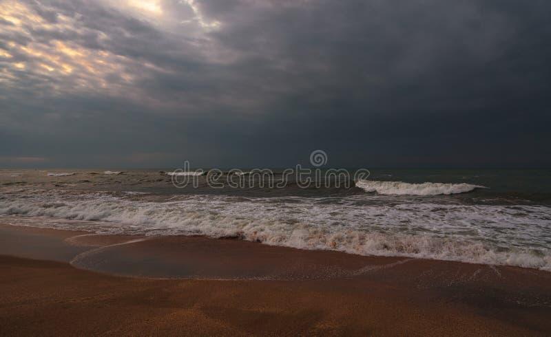 黑暗的风雨如磐的海和空的海滩 库存照片