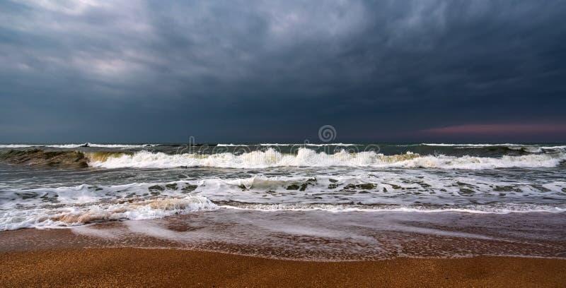 黑暗的风雨如磐的海和空的海滩 库存图片