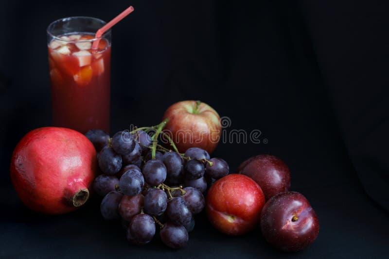 黑暗的食物-单色画石榴、葡萄、苹果和李子与果汁喷趣酒 库存图片