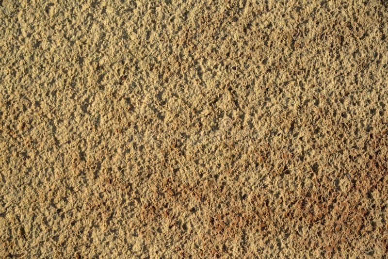 黑暗的黄色硅土沙子,背景纹理  图库摄影