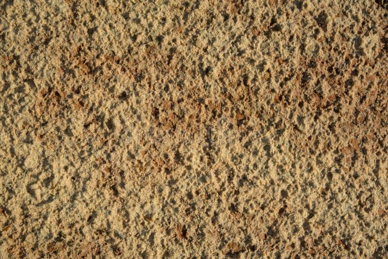黑暗的黄色硅土沙子,背景纹理  库存图片