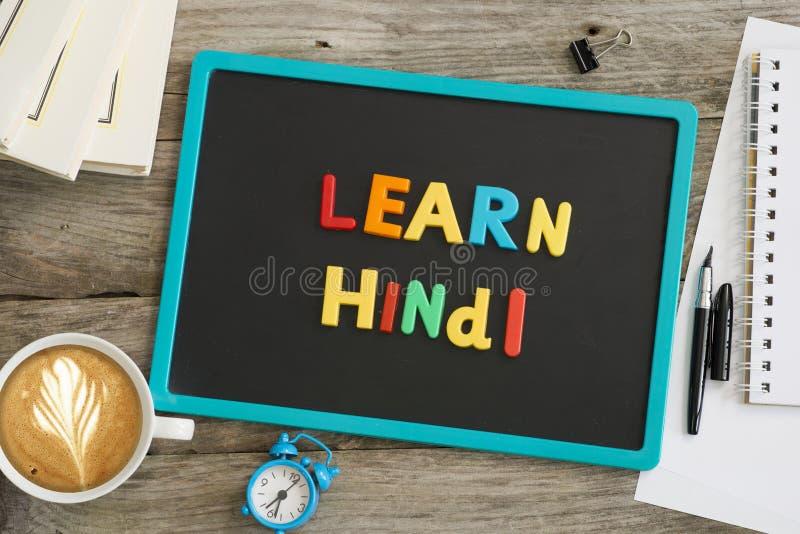 黑暗的黑板与学会从五颜六色的塑料信件的北印度语消息 库存照片