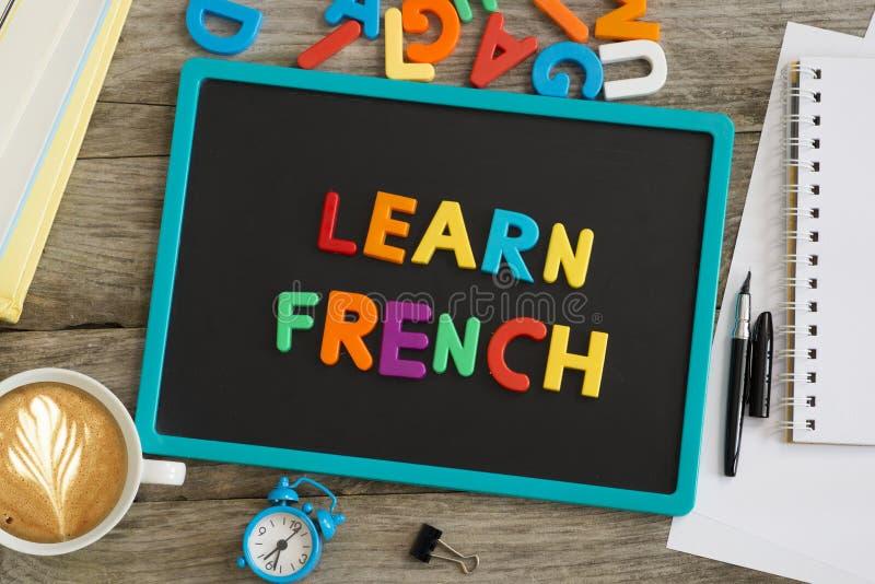 黑暗的黑板与学会从五颜六色的塑料信件的法国忠告 免版税图库摄影