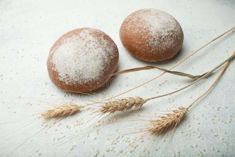 黑暗的黑麦面包两个小圆面包洒与在白色背景的面粉与麦子或黑麦的小尖峰 库存照片