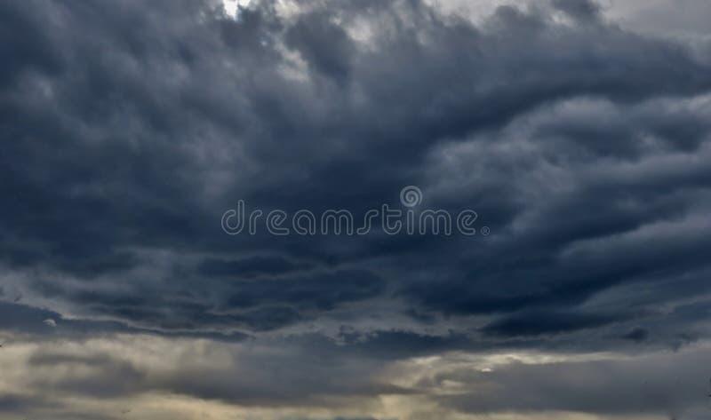 黑暗的-蓝色-灰色颜色巨大的邪恶的云彩与太阳击穿的光芒的  库存照片