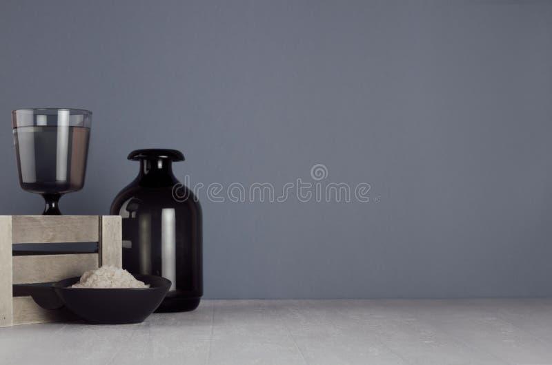 黑暗的minimalistic卫生间装饰-墨镜花瓶、木箱子、碗有化妆用品盐的在白色木桌上和灰色墙壁 图库摄影