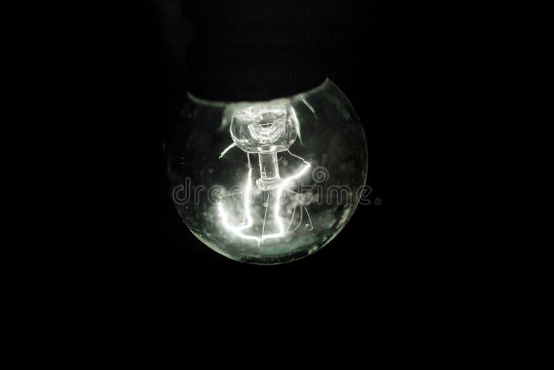 黑暗背景中发光的复古灯泡 免版税库存照片