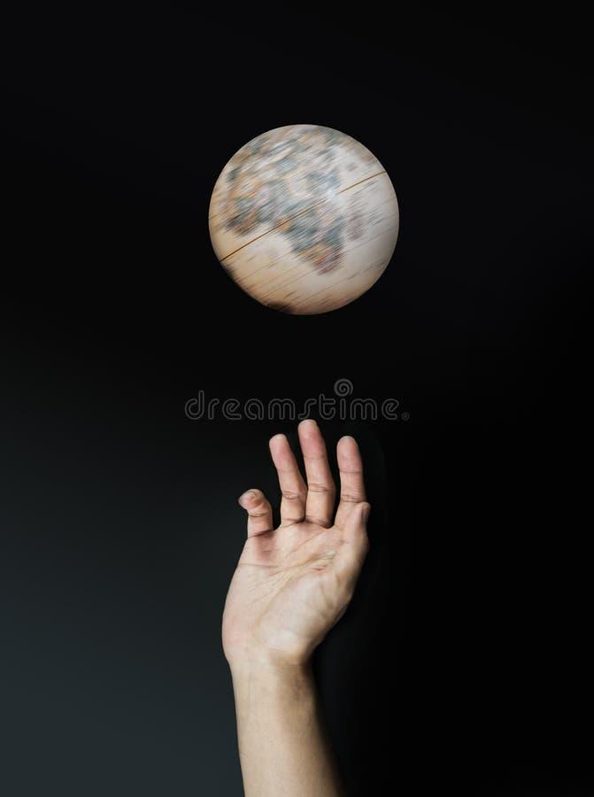黑暗被影响的转动的地球和手到达 免版税库存照片