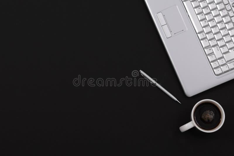 黑最低纲领派与拷贝空间的家庭办公室书桌笔咖啡膝上型计算机顶视图 库存照片