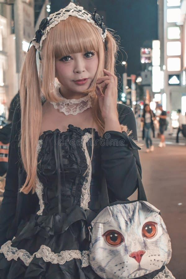 黑服装和白肤金发的潜水的头发的日本女孩走在典型的日语的东京日本例子中的原宿的 免版税库存图片