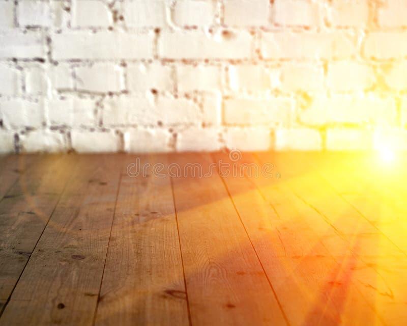 黑木地板和白色砖墙背景 复制与太阳光光晕的空间 定调子 免版税库存图片