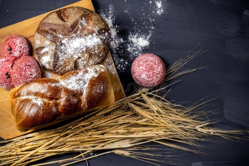 黑木桌上摆着各种新鲜出炉的面包,包括麦穗和巧克力红曲奇饼 顶视图 免版税库存图片
