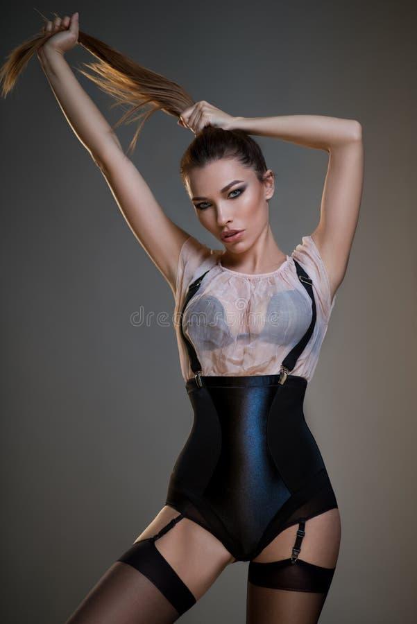 黑束腰、白色女衬衫和悬挂装置的美丽的少妇 免版税库存图片