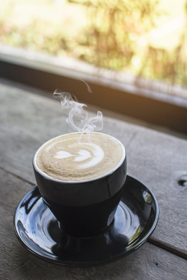 黑杯子在木桌上的热的咖啡在窗口附近 库存图片