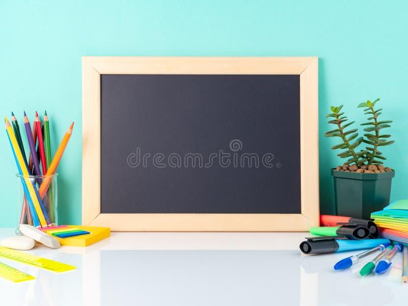 黑板和学校用品在白色桌上由蓝色墙壁 免版税库存图片