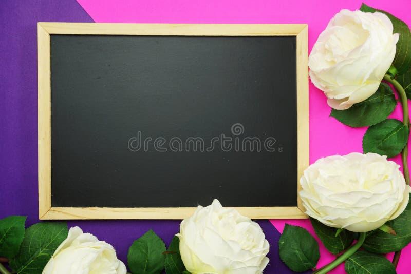 黑板和束在桃红色和紫色背景平的位置的牡丹花 免版税库存照片