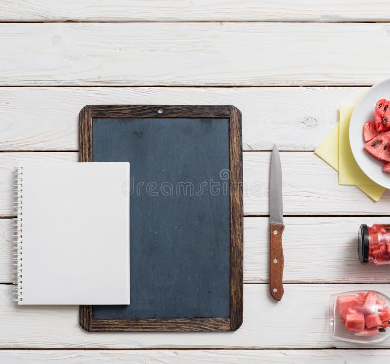 黑板和笔记本在一张书桌上用西瓜 库存图片