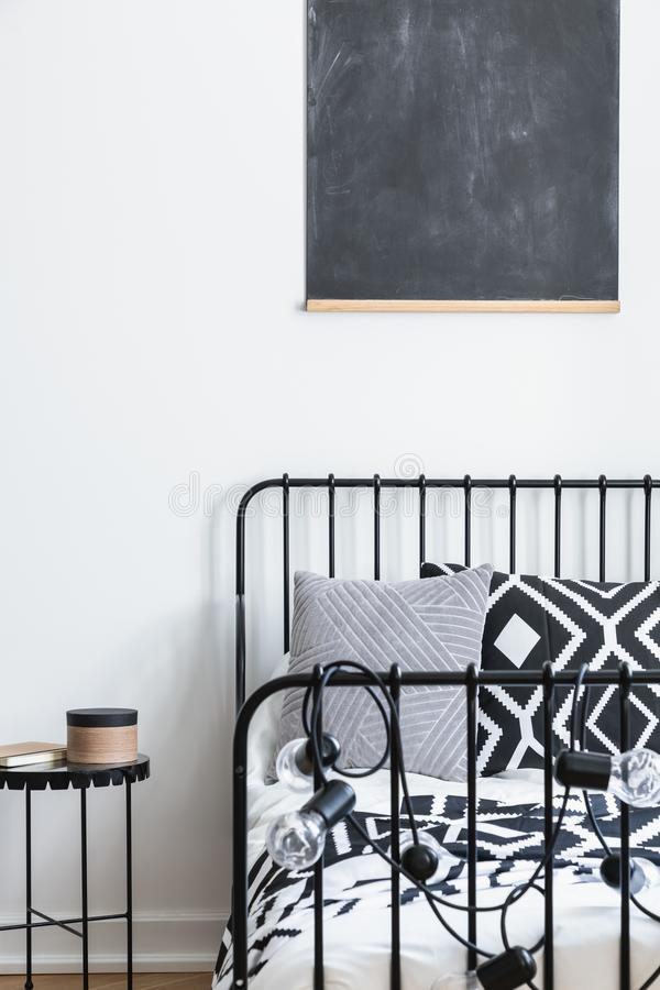 黑板垂直的看法在少年卧室墙壁上的有黑白被仿造的卧具的在唯一金属床上,真正 免版税库存照片