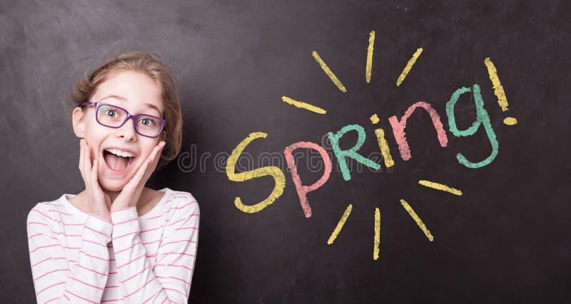 黑板的激动的女孩有五颜六色的'春天的!'标志 免版税图库摄影