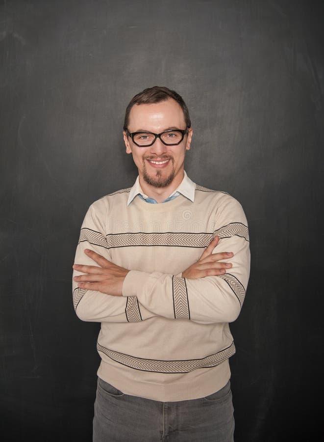 黑板背景的微笑的愉快的老师 免版税图库摄影