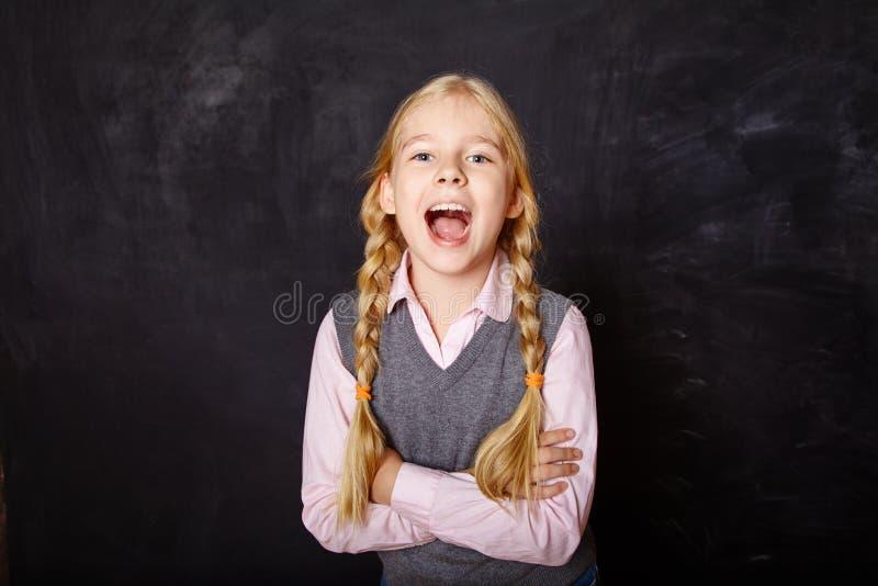 黑板背景的滑稽的女小学生 库存图片