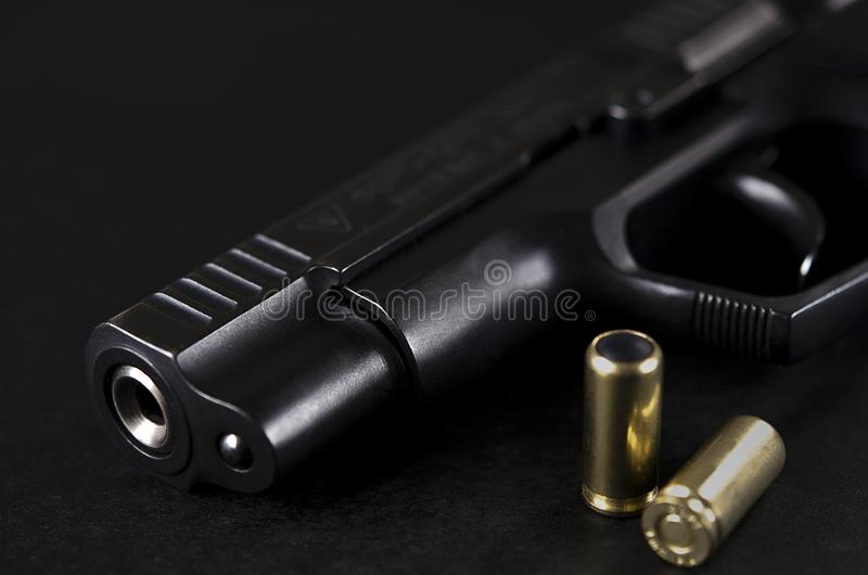 黑枪在黑背景说谎在子弹旁边 免版税库存照片