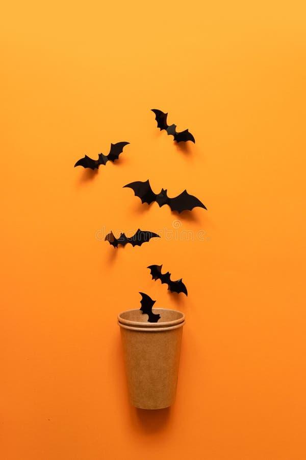 黑棒的万圣节概念飞行在橙色背景的纸杯外面 库存照片