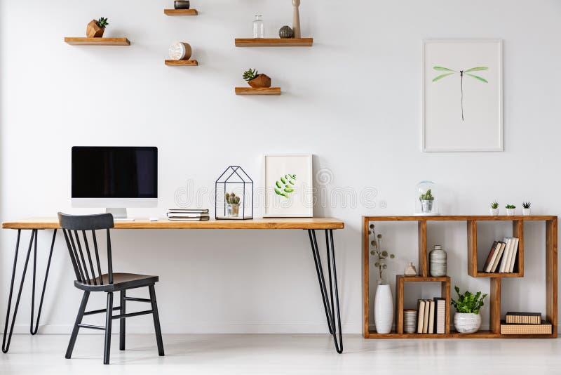 黑椅子在与计算机显示器的桌上在明亮的家庭办公室 图库摄影