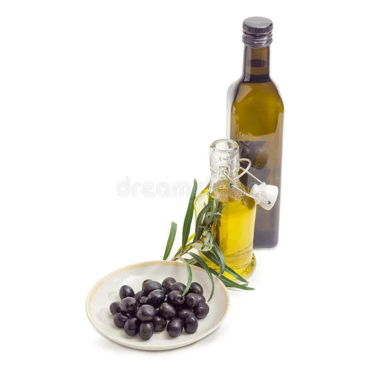 黑橄榄、两个瓶橄榄油和橄榄树枝 免版税图库摄影