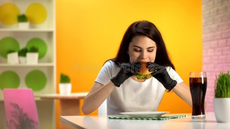黑橡胶手套的年轻女人吃水多的汉堡包的坐在咖啡馆桌上 免版税库存照片