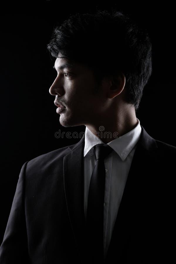 黑正式衣服的亚裔人在黑暗 免版税库存照片