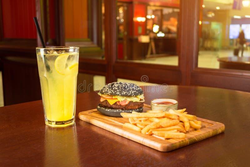 黑汉堡炸薯条和一个杯子用西红柿酱在一个木板,有一杯的柠檬水切片柠檬和小管 免版税库存照片