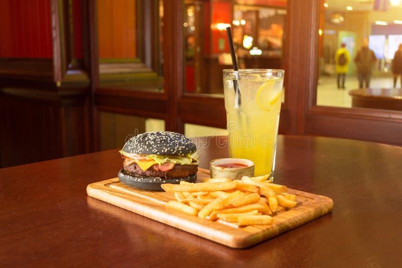 黑汉堡炸薯条和一个杯子用西红柿酱在一个木板,有一杯的柠檬水切片柠檬和小管 库存图片