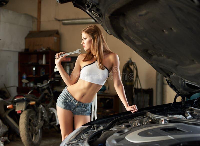 黑汽车性感的近女孩开放敞篷在车库的 库存图片