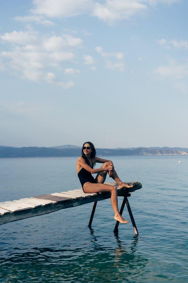 黑泳装的可爱的妇女在码头 免版税图库摄影
