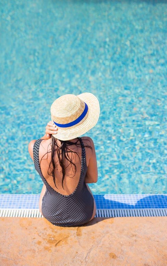 黑泳装的美丽的女孩在一个蓝色水池附近 库存照片