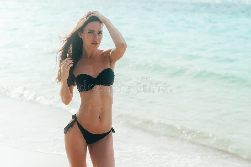 黑泳装的美女在白色沙滩走在海洋附近 库存照片