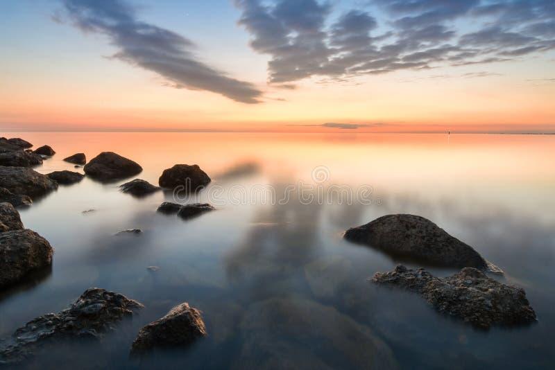 黑海多岩石的海滩风平浪静在日落以后的,阿纳帕,俄罗斯 免版税库存照片